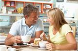 Couple Enjoying Slice Of Cake And Coffee In CafŽ