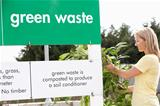 Woman At Recycling Centre Disposing Of Garden Waste