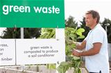 Man At Recycling Centre Disposing Of Garden Waste