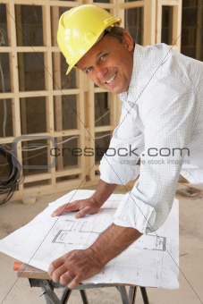 Architect Studying Plans In New Home
