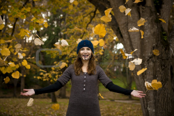 Happy woman in a beautiful autumn day watching the leaves falling