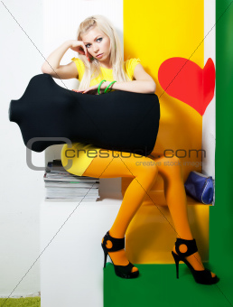 Beauty young female blond hair sitting witn dummy