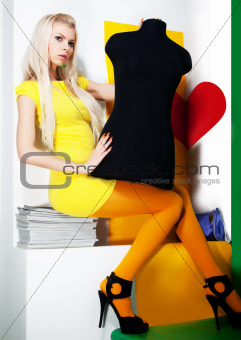 Lovely young girl blond hair with black dummy sitting