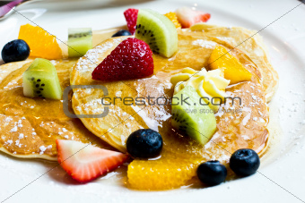 Fresh fruit pancakes with honey syrup.