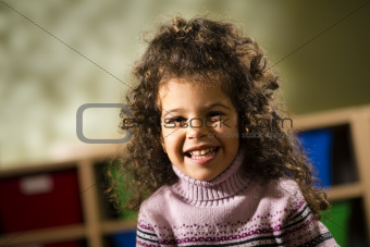 Happy child smiling for joy at camera in kindergarten