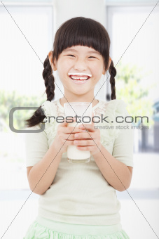 Happy  little girl holding a glass of fresh milk