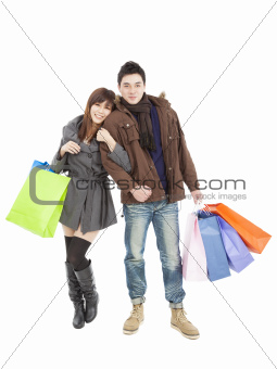 happy young asian couple with shopping bags isolated on white