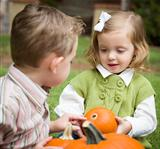 Cute Young Brother and Sister Children Enjoying the Pumpkins at the Pumpkin Patch.