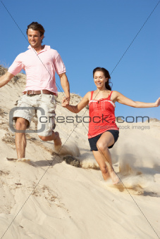 Couple Enjoying Beach Holiday Running Down Dune