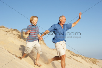Grandfather And Grandson Enjoying Beach Holiday Running Down Dune