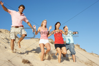 Group Of Friends Enjoying Beach Holiday Running Down Dunes