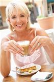 Senior Woman Enjoying Coffee And Cake In CafŽ