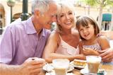 Grandparents With Granddaughter Enjoying Coffee And Cake In CafŽ