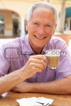 Senior Man Enjoying Coffee And Cake In CafŽ