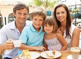 Young Family Enjoying Cup Of Coffee And Cake In Caf Together