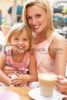 Mother And Daughter Enjoying Cup Of Coffee And Piece Of Cake In CafŽ