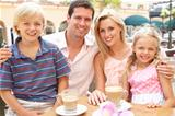Young Family Enjoying Cup Of Coffee In CafŽ Together