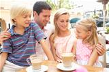 Young Family Enjoying Cup Of Coffee In Caf Together