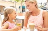 Mother And Daughter Enjoying Cup Of Coffee And Juice In Caf Together