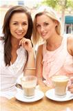 Two Young Women Enjoying Cup Of Coffee In CafŽ