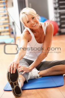 Senior Woman Doing Stretching Exercises In Gym