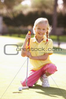 Young Girl Practising Golf On Putting On Green