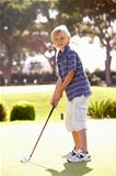 Young Boy Practising Golf On Putting On Green