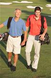 Two Men Walking Along Golf Course Carrying Bags