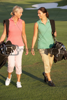 Two Women Walking Along Golf Course Carrying Bags