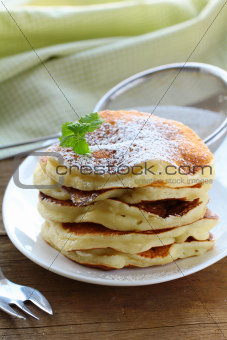 traditional American pancakes on a plate with powdered sugar