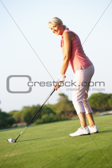 Senior Female Golfer Teeing Off On Golf Course
