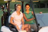 Two Female Golfers Riding In Golf Buggy On Golf Course