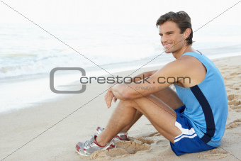 Young Man In Fitness Clothing Resting After Exercise On Beach