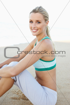 Young Woman In Fitness Clothing Resting After Exercise On Beach