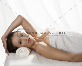 pretty girl lying on a table with towel and hand on the head