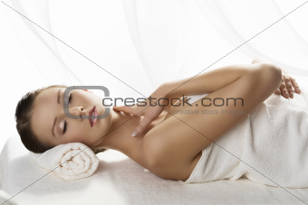 pretty girl lying on a table with towel with closed eyes