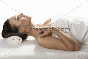 pretty girl lying on a table with towel in profile