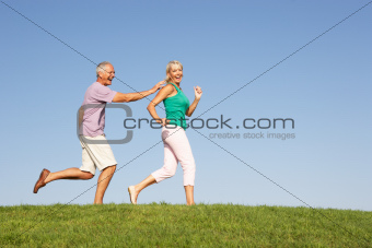 Senior couple running though field