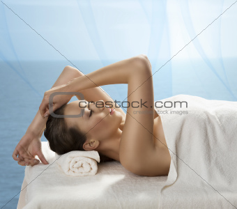 pretty girl lying on a table with towel with expression of pleas