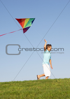 Young boy runs with kite through field
