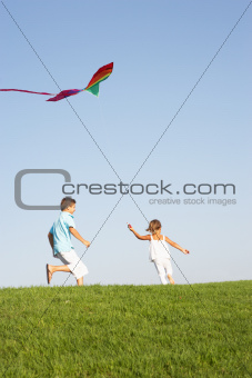 Young children run with kite through field