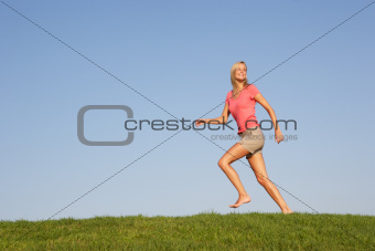 Young woman running through field