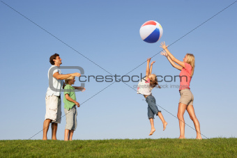 Young family, parents with children,  playing in a field