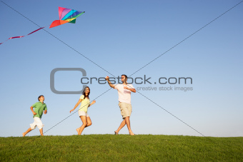 Young family, parents with child, playing in a field