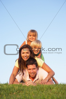 Young parents, with children, posing on a field