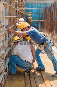 Construction builders positioning concrete formwork frames