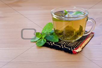 green tea with mint on wooden table