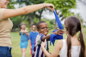 Children and teacher playing games in city park