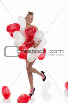 blonde girl with many balloons on her body. she smiles