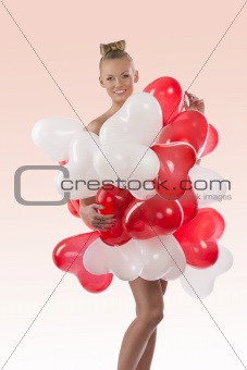 blonde girl with many balloons on her body, she touches those